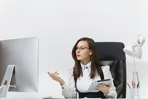 Beautiful serious engrossed brown-hair business woman in suit and glasses sitting at the desk, working at computer with modern monitor with documents and tablet in light office on white background