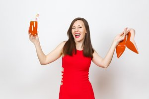 Beautiful glamour fashionable young brown-hair woman in red dress holding glass of drink cocktail, beige shoes with red sole of her shopping isolated on white background. Copy space for advertisement.