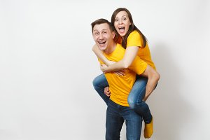 Fun inspired young couple, woman sit on man piggyback, fans in yellow cheering favorite team, expressive gesticulating hands isolated on white background. Sport, family leisure, lifestyle concept.