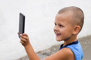 Child with a smartphone. A little boy shoots video on a smartphone.