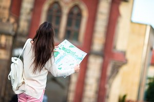 Tourist girl with citymap walking on european streets. Travel caucasian woman with map outside during holidays in Europe.