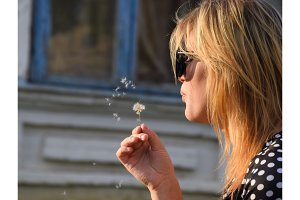 Girl blowing on a dandelion. Blowing of dandelion seeds
