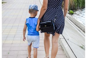 Mom and son are walking around the park in the hand. Back view. Mother in a dress