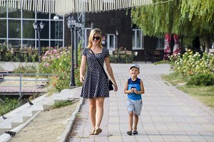 Mother and son are walking in the park. Family walk
