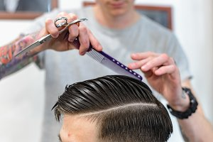 Men's hair care. Haircut in barbershop. Barber makes a beautiful hairstyle for the client.