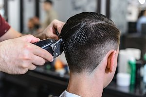 Interior shot of working process in barbershop. Side view of handsome young man getting trendy beard haircut in modern barbershop. Cool male hairstylists serving clients