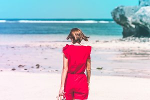 Girl in a red dress walking barefoot on the sea shore. Tropical beach, Bali island. Sunny day.