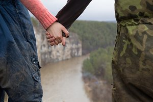 Hands of young couple hikers standing on the edge of a cliff over the mountain river