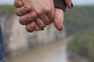 Hands of young couple hikers standing on the edge of a cliff over the mountain river - close up