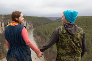 Rear view of couple hikers standing on the edge of a cliff over the mountain river and holds hands each other