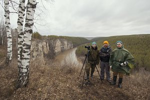 Three young friend camermen outdoor - filmmaking on wild mountain forest