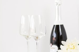 Champagne and two glasses on a white