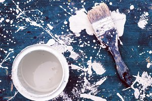Open can of white paint with brush
