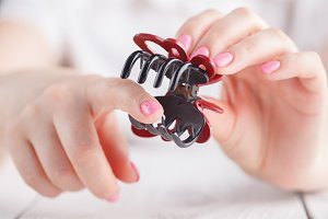 Human's hand holding hairclip opened