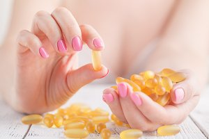 women holding a fish oil capsule