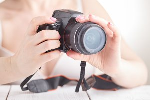 Female hold SLR photo camera in hand