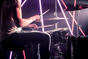 the man plays the drums. Against the background of colored lights and a bright beam of light.