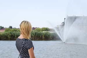 Portrait of a girl against a lake and a fountain. Beautiful blonde