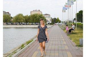 The blonde girl walks on the sidewalk along the lake