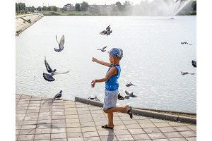 The boy runs along the lake promenade and chases pigeons