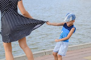 The little boy looks under his skirt. Children's pranks. The boy is playing with his mother