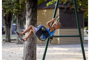 The little boy swings on the swing himself
