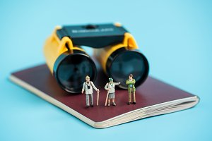 miniature traveler and binoculars on