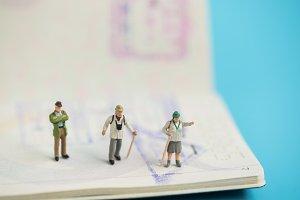 miniature traveler on passport book