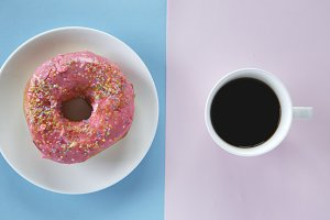 pink sprinkles donut and black coffee with copy space