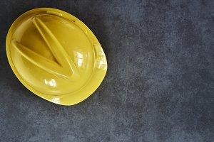 Yellow building helmet on wooden board
