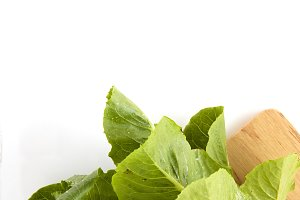 Close-up on a wooden table is a wooden cutting board on Cos lettuce