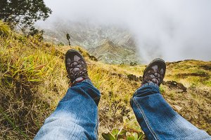 Traveler hiking boots over impressive verdant Xo-Xo valley with mountain peaks, rugged cliffs in fog on Santo Antao Island, Cape Verde