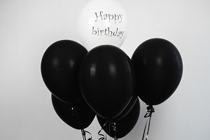 Black and white balloons with birthday greetings