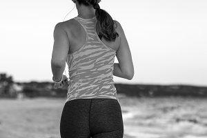 young sportswoman on beach in evening jogging