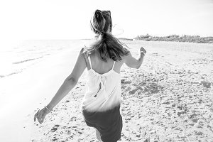 young woman in dress on beach in evening walking