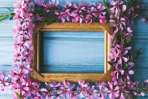 Spring flowers and frame on a blue wooden background