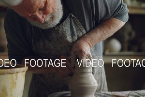 Hard-working senior potter is wetting hands in bowl with water and touching clay jar on spinning throwing-wheel. Bearded man is concentrated on work.