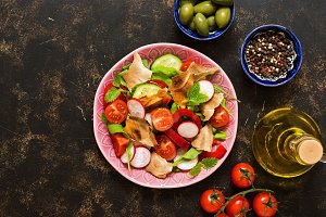 Salad of fresh vegetables with bread fattoush closeup. Arabic dish fattoush on a dark background, top view.