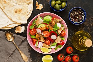 Arabic dish salad fattoush. Pita bread, tomatoes and seasonings. View from above.