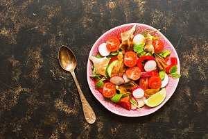 Salad with Arabic bread fattoush on a brown background, top view. Copy space.