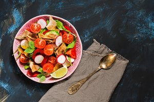 Salad of fresh vegetables with Arabic bread fattoush on a blue background, top view. Copy space.