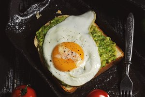 Avocado smeared on toast, top fried egg, rustic style, top view. Toned photo.