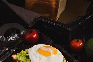 Sandwich with avocado and fried egg in country style. Delicious healthy breakfast.