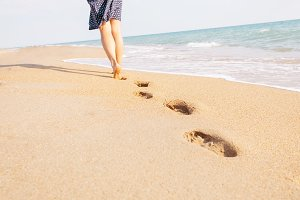 Barefoot woman walking on beach