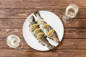 Fish dish with glasses of wine.