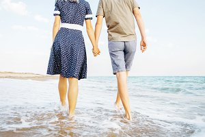 Young couple walking on beach.