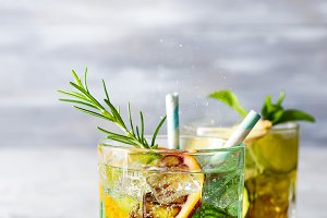 Summer mint lime refreshing cocktail mojito with rum and ice in glass on stone background