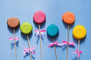 French biscuit macaron on a stick with a bow on a blue painted background.Creative art work