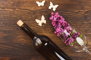 Wineglass with lilacs and different decorations on the wooden background