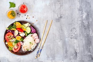 Spicy glass Rice noodles and vegetables salad on stone background